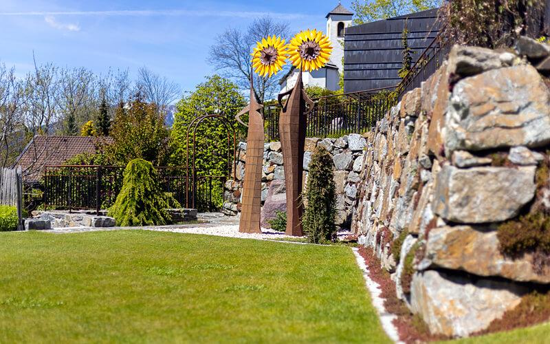 Anwesen Österreich Iselsberg: Garten / Rasenfläche mit Sonnenblumen-Skulpturen. Fotograf: Martin Lugger (remax)