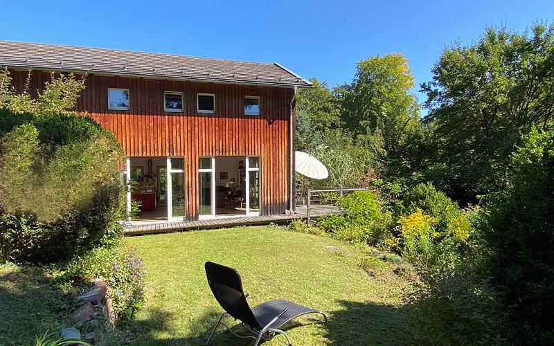 Feldafing: Verkauf Holzhaus. Aussenansicht mit Garten und Liegestuhl. ©Quartiere Ulrike Küpper